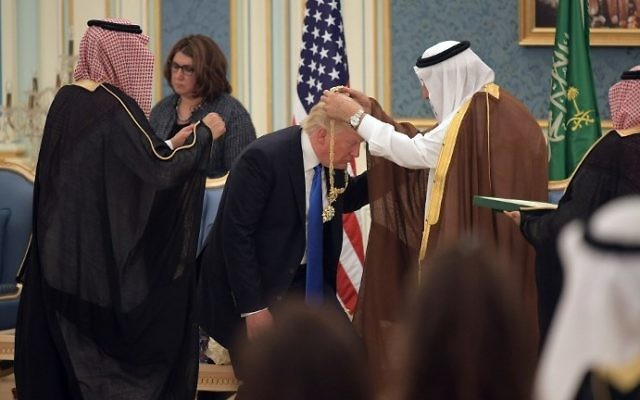 US President Donald Trump (C) receives the Order of Abdulaziz al-Saud medal from Saudi Arabia's King Salman bin Abdulaziz al-Saud (R) at the Saudi Royal Court in Riyadh on May 20, 2017. (AFP PHOTO / MANDEL NGAN)