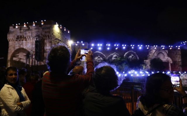 People watch on May 20, 2017, the iconic photo taken by David Rubinger of Israeli paratroopers standing next to the Western Wall on June 1967 during an audio slideshow projected on the ancient walls of Jerusalem's Old City on the beginning of the week marking the 50th anniversary of the 1967 Israeli-Arab War.  (AFP PHOTO / GALI TIBBON)