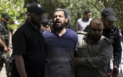 Hamas security forces escort Hisham al-Aloul (C), a 44-year-old Palestinian man convicted of the murder of Hamas terror chief Mazen Faqha, out of the military court in Gaza City on May 21, 2017. (AFP Photo/Mahmud Hams)