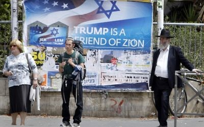 Israelis walks past a poster welcoming and supporting US President Donald Trump in downtown Jerusalem, on May 21, 2017, on the eve of a two-day visit of the US president. (AFP/ MENAHEM KAHANA)