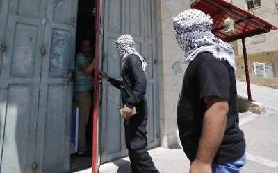 Palestinian Fatah movement supporters speak to a shop owner as they roam the streets of the West Bank town of Bethlehem to monitor a general strike called for by activists throughout the Palestinian territories and among Arab Israelis, in support of Palestinian prisoners on hunger-strike in Israeli jails, May 22, 2017. (AFP/Musa AL SHAER)