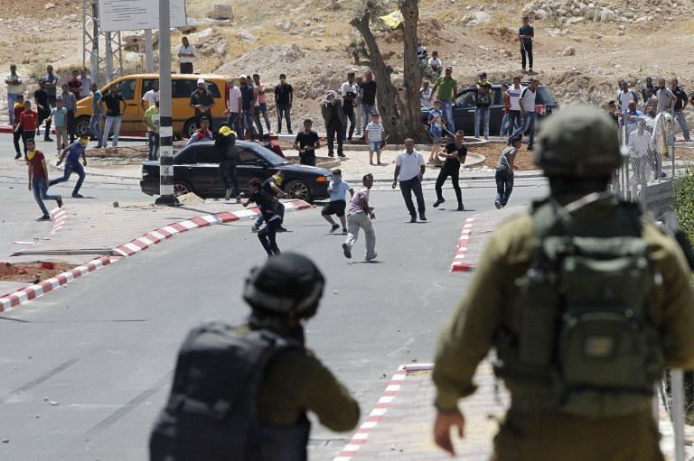 Israeli security forces clash with Palestinian rioters at the northern entrance of the village of Yatta, near Hebron, in the West Bank, on May 22, 2017. (Hazem Bader/AFP)