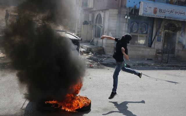A Palestinian man throws stones at Israeli security forces during clashes in the West Bank city of Qalandiya, north of Jerusalem, on May 22, 2017. (Abbas Momani/AFP)