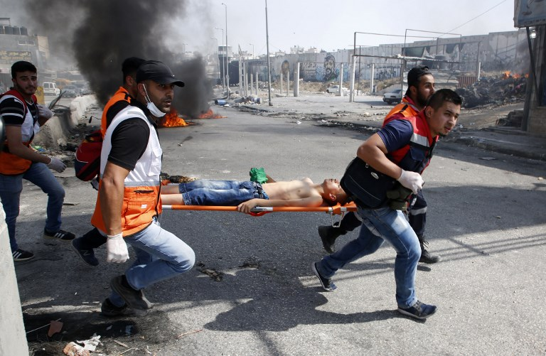 Palestinian medics carry away a protester who was injured during clashes with Israeli security forces in the West Bank city of Qalandiya, north of Jerusalem, on May 22, 2017. (Abbas Momani/AFP)