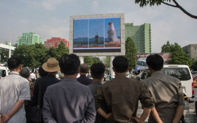 People watch a screen showing news coverage of the Pukguksong-2 missile rocket launch at a public square in central Pyongyang on May 22, 2017. (Kim Won-Jin/AFP)