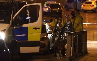 Concert goers wait to be picked up at the scene of a  terror attack during a pop concert by US star Ariana Grande in Manchester, northwest England on May 23, 2017. (AFP/Paul Ellis)