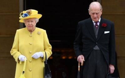 Britain's Queen Elizabeth II and Britain's Prince Philip, Duke of Edinburgh observe a minute's silence at the start of a Special Garden Party at Buckingham Palace in London on May 23, 2017. (AFP Photo/Pool/Dominic Lipinski)