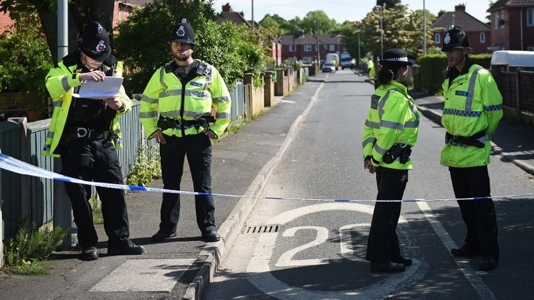 Police officers stand on duty on a cordoned-off road in the Fallowfield neighborhood of Manchester on May 23, 2017, as they search a nearby residential property following the May 22 deadly terror attack at the Ariana Grande concert at the Manchester Arena. (AFP Photo/Oli Scarff)