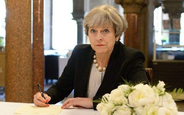 Britain's Prime Minister Theresa May writes a message in a book of condolence at Manchester Town Hall in Manchester, northwest England, on May 23, 2017, following the terror attack at the Ariana Grande concert at the Manchester Arena in Manchester on May 22. (AFP / POOL / Ben Birchall)