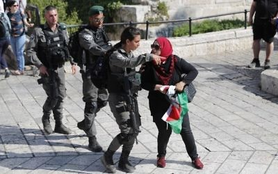 Border Police officers clear a woman with a Palestinian flag from outside Damascus Gate in Jerusalem's Old City on May 24, 2017, ahead of the annual Jerusalem Day march.  (AFP Photo/Thomas Coex)