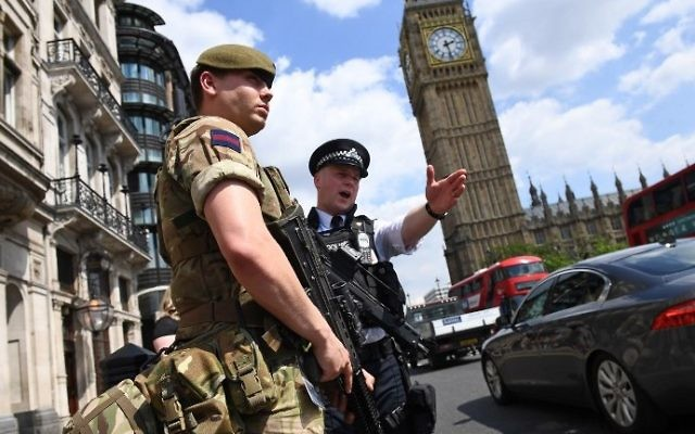 A British Army soldier patrols with an armed police officer near the Houses of Parliament in central London on May 24, 2017. AFP/ Justin TALLIS)