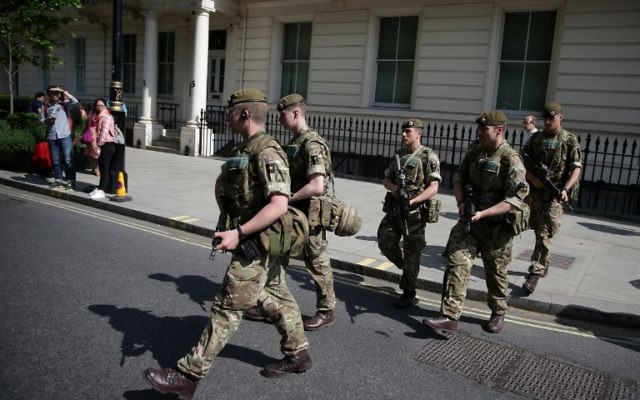 British Army soldiers are led by a police officer into Buckingham Palace in central London on May 24, 2017. (AFP PHOTO / Daniel LEAL-OLIVAS)