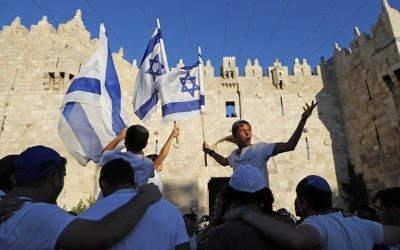 Israelis wave the Israeli flag as they parade in front of Damascus Gate in Jerusalem's Old City on May 24, 2017 to commemorate Jerusalem Day, marking the reunification of the city following the 1967 Six Day War. (AFP/Thomas Coex)