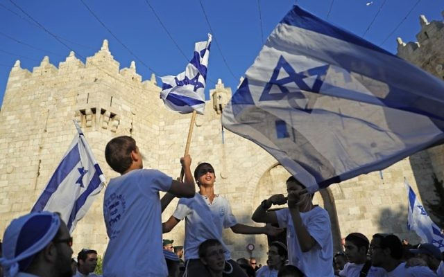 Israelis wave the Israeli flag as they parade outside Damascus Gate in Jerusalem's Old City on May 24, 2017 to commemorate Jerusalem Day, marking the reunification of the city following the Six-Day War of 1967. (AFP PHOTO / Thomas COEX)