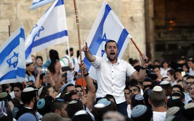 Israelis wave Israeli flags as they parade around Jerusalem's Old City on May 24, 2017 to commemorate Jerusalem Day, marking the reunification of the city following the Six-Day War of 1967. (AFP PHOTO / Menahem KAHANA)