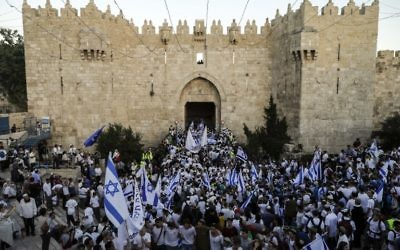 Israelis wave the Israeli flag as they parade through Damascus Gate in Jerusalem's Old City on May 24, 2017 to commemorate Jerusalem Day, marking the reunification of the city following the Six-Day War of 1967. (AFP PHOTO / Menahem KAHANA)