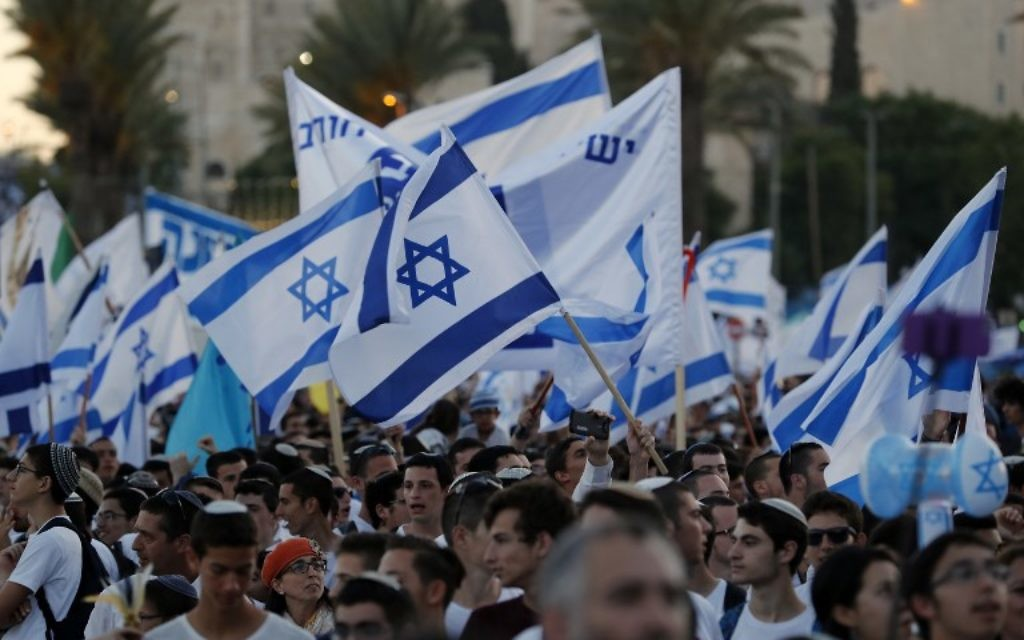 Illustrative: Israelis wave Israeli flags as they parade around Jerusalem's Old City on May 24, 2017 to commemorate Jerusalem Day, marking the reunification of the city following the Six-Day War of 1967. (AFP PHOTO / Menahem KAHANA)