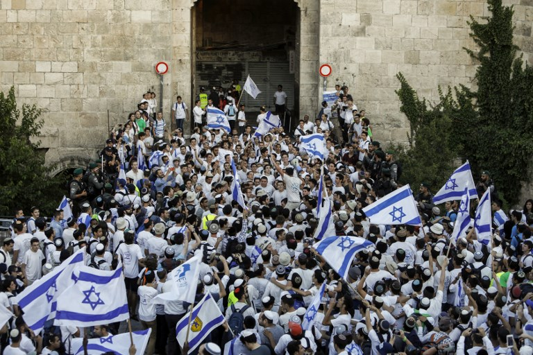 Israelis wave the Israeli flag as they parade through Damascus Gate in Jerusalem's Old City on May 24, 2017 to commemorate Jerusalem Day, marking the reunification of the city following the Six-Day War of 1967. (AFP PHOTO / Thomas COEX)