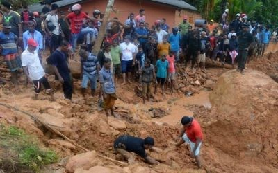Sri Lankan military rescue workers and villagers search for survivors at the site of a mudslide in Bellana village in Kalutara on May 26, 2017. (Lakruwan Wanniarachchi/AFP)
