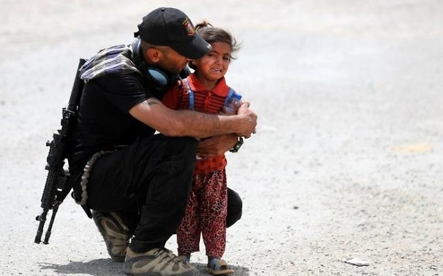 An Iraqi soldier helps a displaced girl after leaving their homes west of Mosul on May 26, 2017, as government forces continue their offensive to retake the city of Mosul from Islamic State (IS) group fighters. (AFP/Karim Sahib)