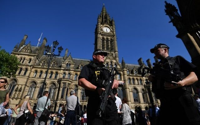 Armed police stand guard in front of the Town Hall in Albert Square during the GreatCity Games in central Manchester, England, on May 26, 2017. (AFP Photo/Ben Stansall)