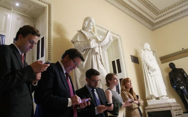 People in Washington look at their devices as news comes in that the Justice Department announced that former FBI director Robert Mueller will be a special counsel overseeing the Russia investigation.  (Mark Wilson/Getty Images/AFP)
