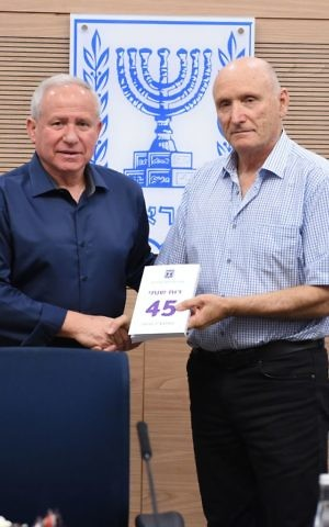 IDF Ombudsman Yitzhak Brick, right, gives MK Avi Dichter a copy of his annual report on May 28, 2017. (Defense Ministry)
