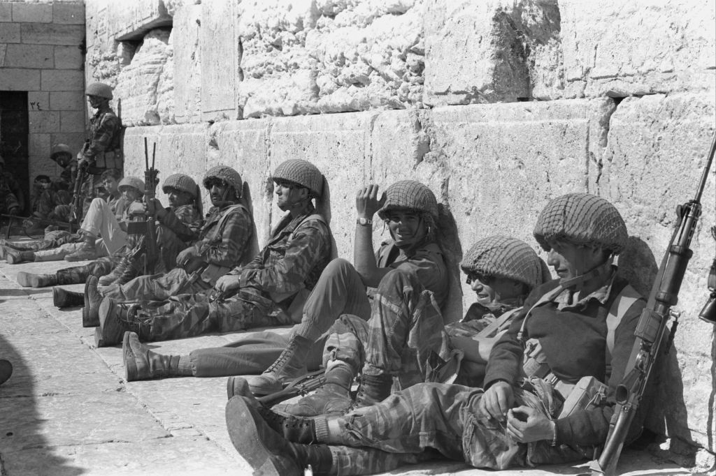 A group of paratroopers sits along the Western Wall in Jerusalem's Old City on June 7, 1967. (Bamahane Magazine/Defense Ministry's IDF Archive)