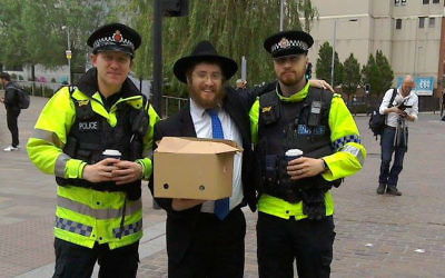 Rabbi Shneur Cohen distributes hot tea and pastries to police working at the scene of Monday night's terror attack in Manchester, United Kingdom, May 23, 2017. (Courtesy Chabad of Manchester City Center)
