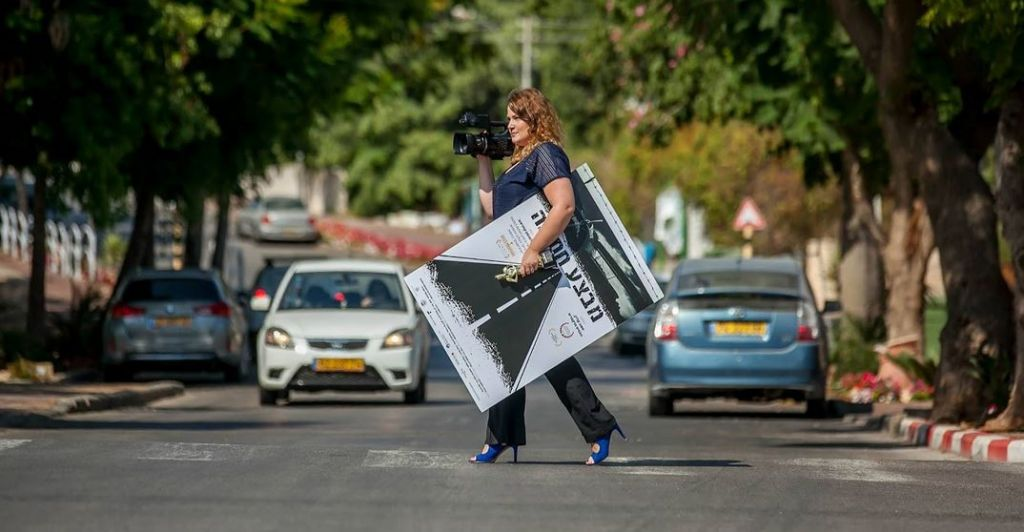 Anat Zalmanson-Kuznetsov crossing the street with the poster for her documentary 'Operation Wedding' and her award in hand. (Eli Itkin)