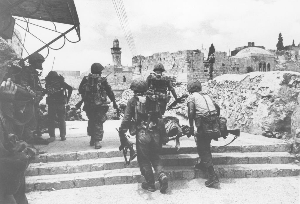 Soldiers carry away an injured comrade on a stretcher through the streets of the Old City of Jerusalem on June 7, 1967. (Defense Ministry's IDF Archive)