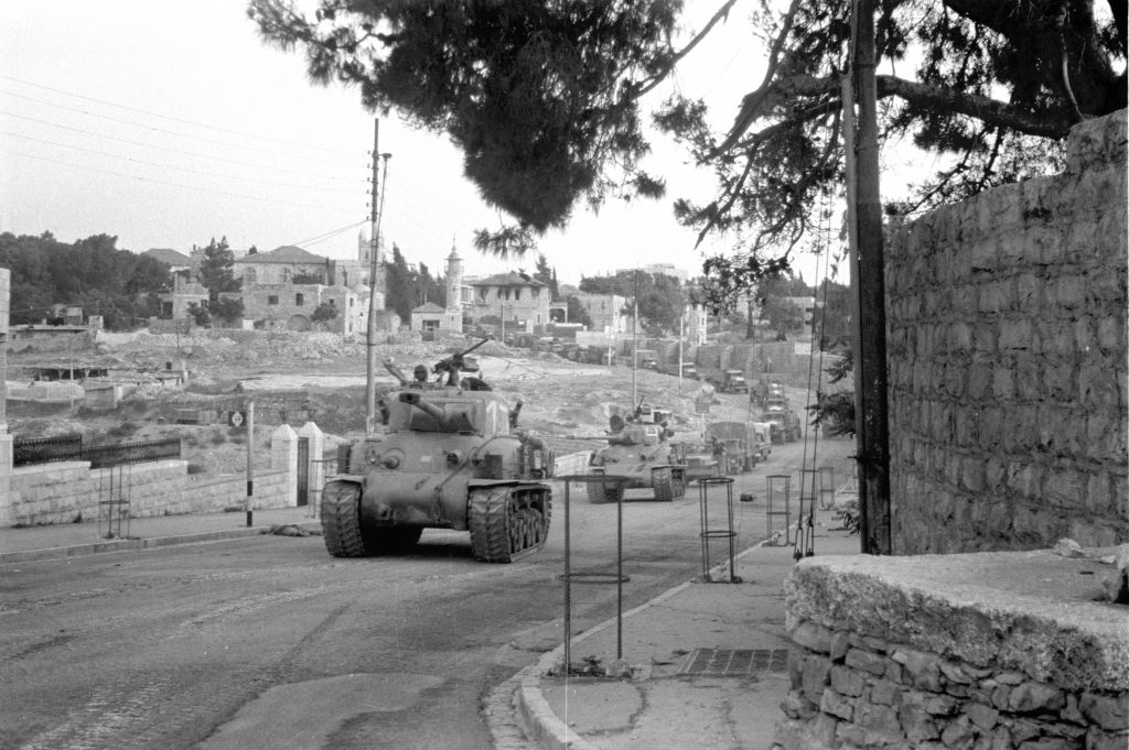 A line of Sherman M-50 tanks and trucks full of soldiers ride towards East Jerusalem to confront the Jordanians on June 5, 1967. (Benny Hadar/Defense Ministry's IDF Archive)