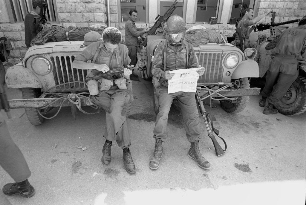 A soldier in the Paratroopers Brigade's reserve reconnaissance company cleans his rifle as his injured comrade reads the newspaper near the Western Wall on June 7, 1967. (Micha Bar-Am/Defense Ministry's IDF Archive)