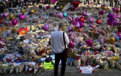 A man stands next to flowers for the victims of Monday's bombing at St Ann's Square in central Manchester, England, Friday, May 26 2017. (AP Photo/Emilio Morenatti)