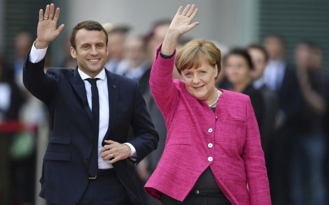 French President Emmanuel Macron, left, and German Chancellor Angela Merkel wave to journalists at the chancellery in Berlin, May 15, 2017. (Bernd von Jutrczenka/dpa via AP)