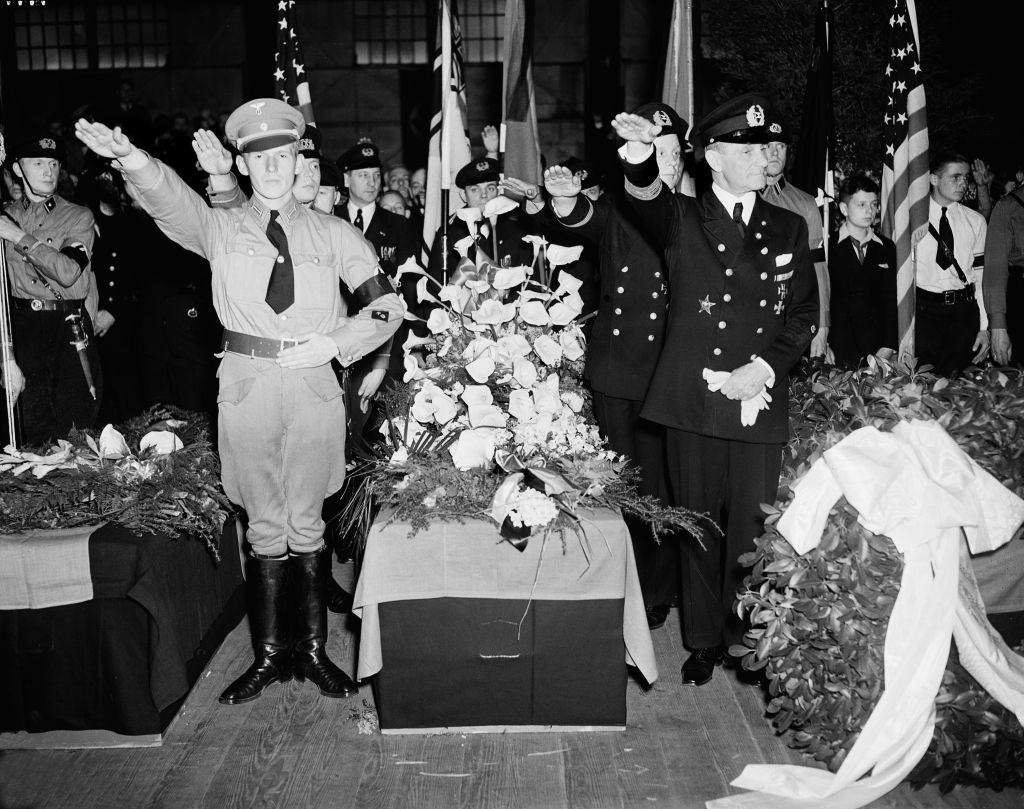 German Nazis give the salute as they stand beside the casket of Capt. Ernest A. Lehmann, former commander of the zeppelin Hindenburg, during funeral services held on the Hamburg-American pier in New York City, May 11, 1937. The caskets of the 28 Germans who lost their lives in the Hindenburg disaster May 6 were placed on board the Hamburg for their return to Europe. (AP Photo/Anthony Camerano)