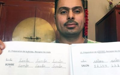 Iraqi refugee Raad Al Azzawi shows a lesson book at the house of his Belgian French tutor in Anderlecht, Belgium on Thursday, May 11, 2017.  (AP Photo/Sylvain Plazy)