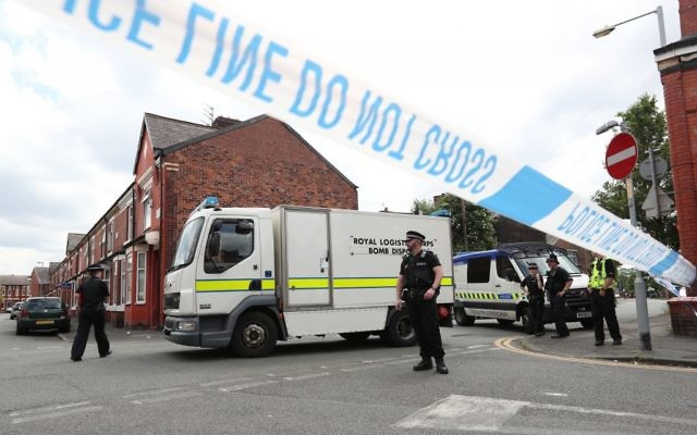 Police and a bomb disposal unit at the junction between Boscombe Street and Yew Tree Road, after an evacuation took place in the Moss Side area of Manchester, England, May 27, 2017. (Jonathan Brady/PA via AP)