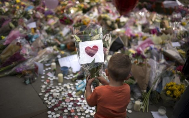 A child places flowers at a memorial site for the victims of the suicide attack at an Ariana Grande concert, set up in a square in central Manchester, Britain, May 24, 2017. (AP Photo/Emilio Morenatti)