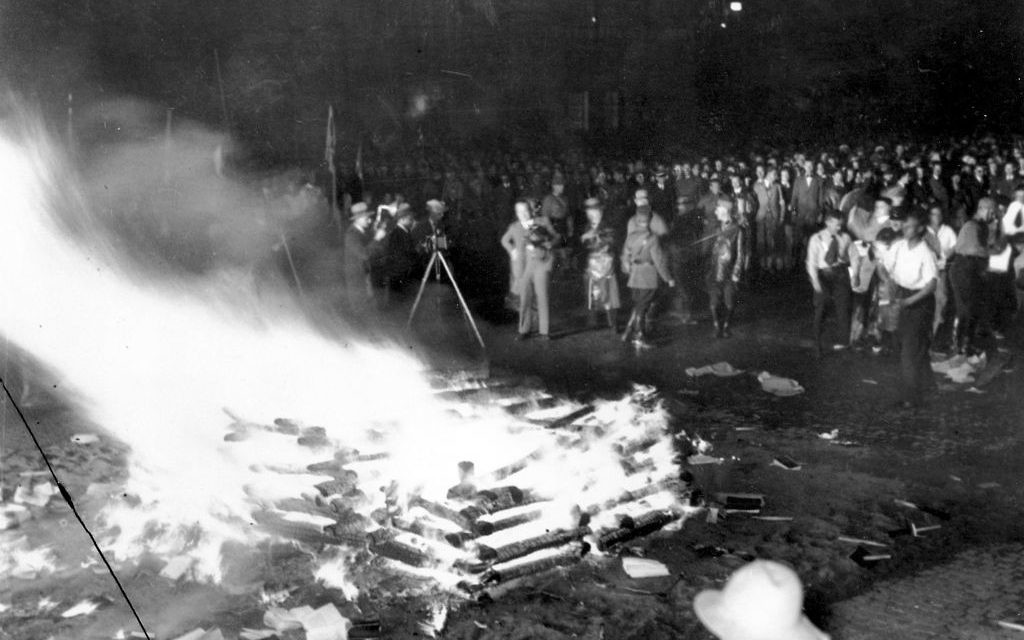 """A crowd gathers to witness thousands of books, considered to be """"un-German,"""" burn in Opera Square in Berlin, Germany, during the Buecherverbrennung book burnings on May 10, 1933. (AP Photo)"""