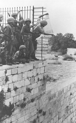 Israeli paratroopers putting up the national flag on the wall of the Temple Mount above the Western Wall in Jerusalem during the Six Day War. (Government Press Office)