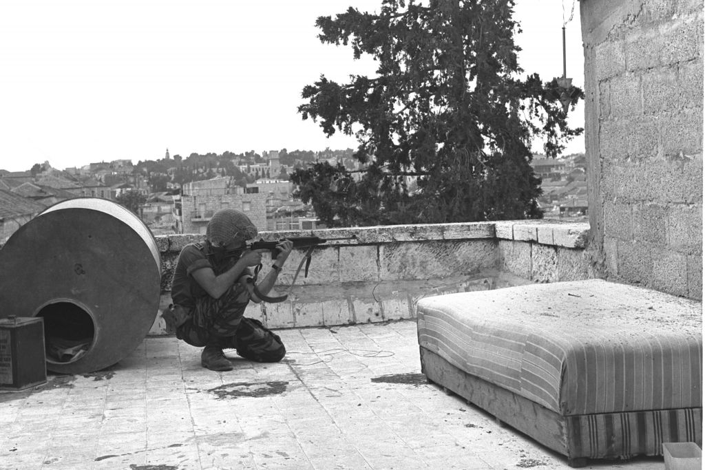 An IDF soldier aiming his rifle at an Arab Legion sniper position in Jerusalem during the Six Day War. (Government Press Office)