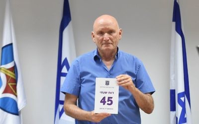 IDF Ombudsman Yitzhak Brick poses with a copy of his annual report on May 28, 2017. (Defense Ministry)