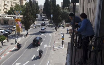 Israelis looking from their balcony as US President Barack Obama's cars arrives at the King David Hotel in Jerusalem on March 20, 2013. (Yonatan Sindel/Flash90)