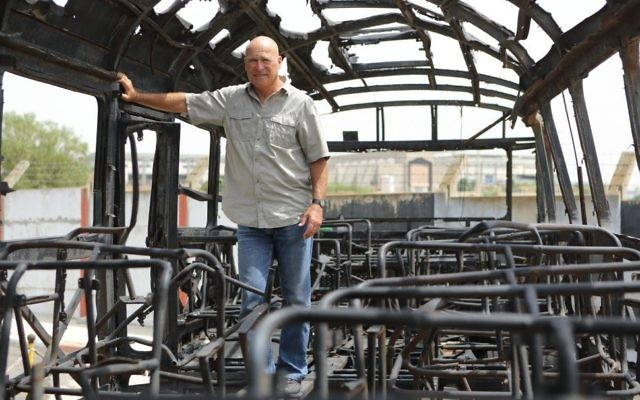 Former Israel Police commissioner Assaf Hefetz stands inside the remains of a bus from a 1978 terror attack known as the Coastal Road Massacre, in a museum in Holon, on May 2, 2013. (Yaakov Naumi/Flash90)