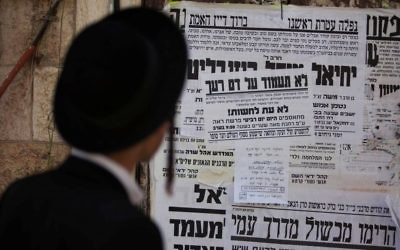 Illustrative: An ultra-Orthodox Jewish man reads a poster calling for the release of a member of Jewish of the anti-Zionist Neturei Karta group on August 1, 2013. (Yonatan Sindel/Flash90)