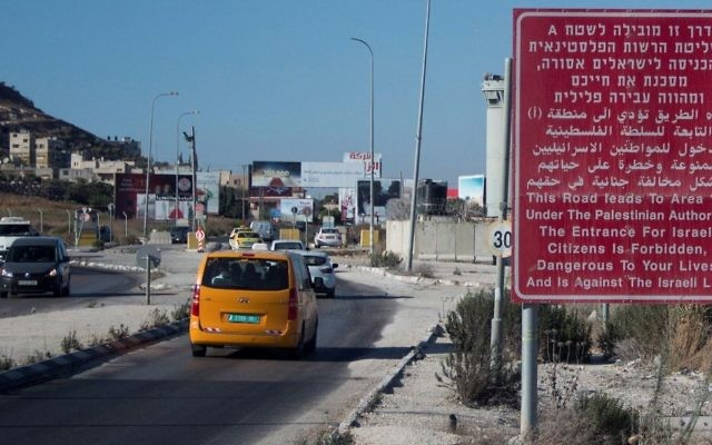 A red sign on the side of a road warns Israeli citizens against entering the West Bank city of Nablus on July 29, 2015. (Garrett Mills/Flash90)