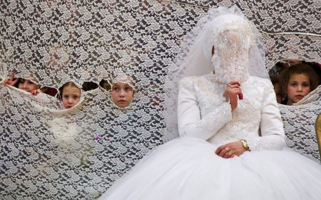 Illustrative: Young girls peek through a curtain next to the bride at an ultra-Orthodox wedding on January 18, 2016. (Yaakov Lederman/Flash90)