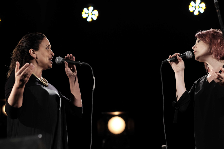 Jewish Israeli singer Ahinoam Nini, left, and Arab Israeli singer Mira Awad, right, perform at an Israeli-Palestinian memorial ceremony in Tel Aviv on April 30, 2017, as Israel marks its annual Memorial Day for fallen soldiers and victims of terror. (Tomer Neuberg/Flash90)