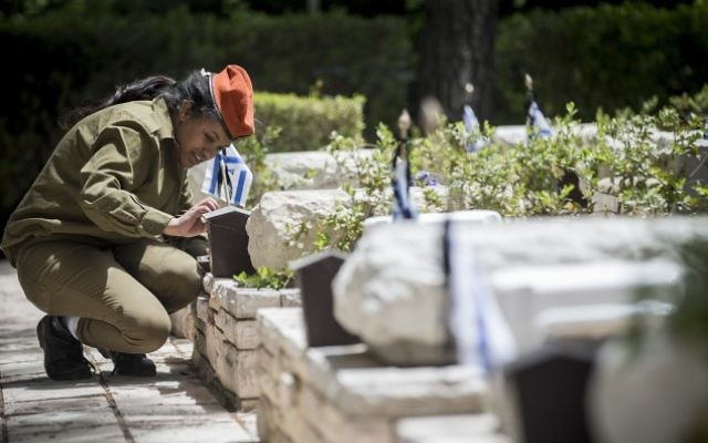 Israeli soldiers light candles near the graves of fallen soldiers at the Mount Herzl Military Cemetery in Jerusalem, on April 30, 2017. (Yonatan Sindel/Flash90)